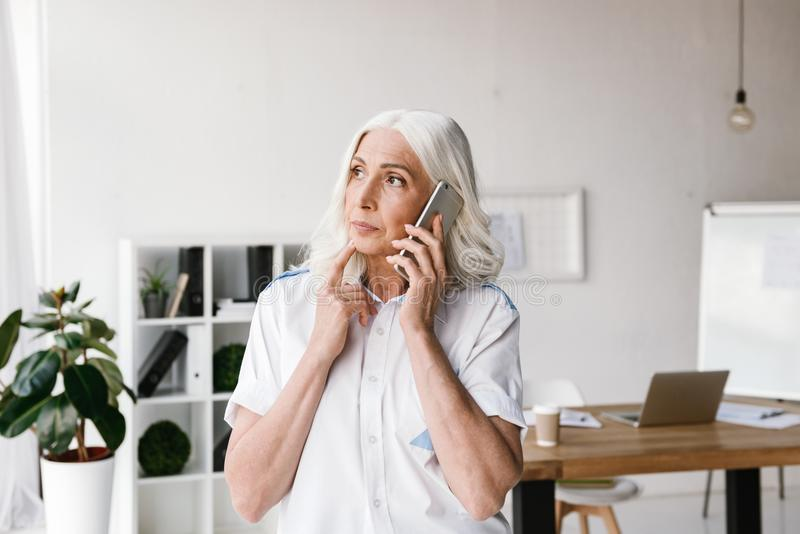 Mature concentrated woman talking by mobile phone. stock photo