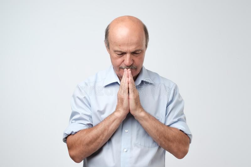 Picture of mature man having put hands together in prayer or meditation, looking relaxed and calm royalty free stock photography