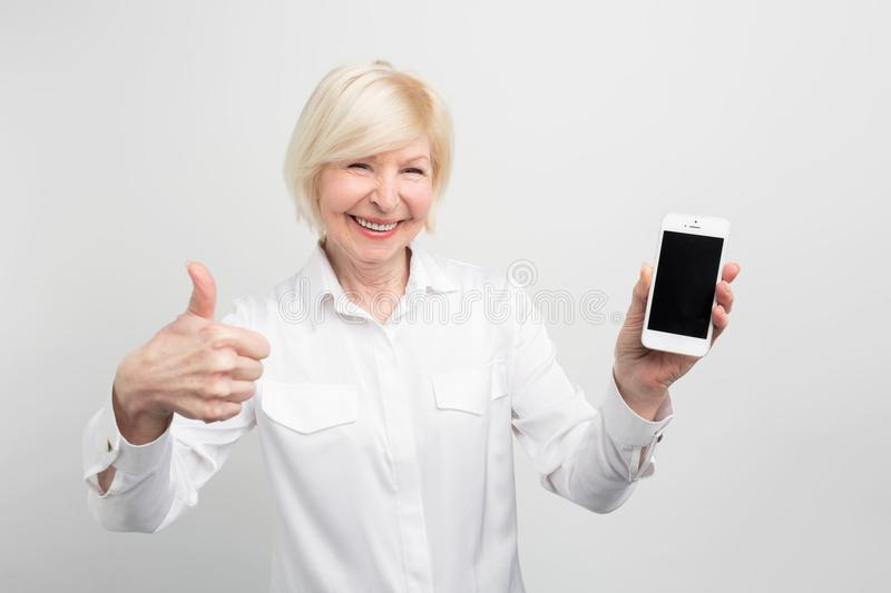 A picture of mature woman with new smartphone. She has tested it and admitted this phone is a good one. That`s why she stock image