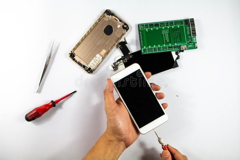 The mobile repairman is starting to check the damaged mobile phone. And brought into repair stock images