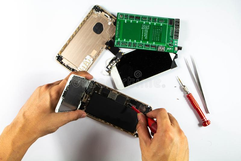 Mobile repair technicians prepare to remove the battery for replacement. royalty free stock photography