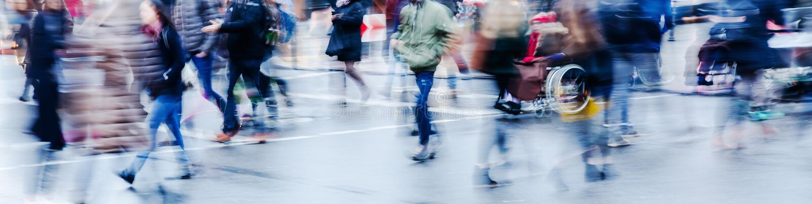 Wintry street scene in the city with people crossing a street. Picture in motion blur of a wintry street scene in the city with people crossing a street royalty free stock photography