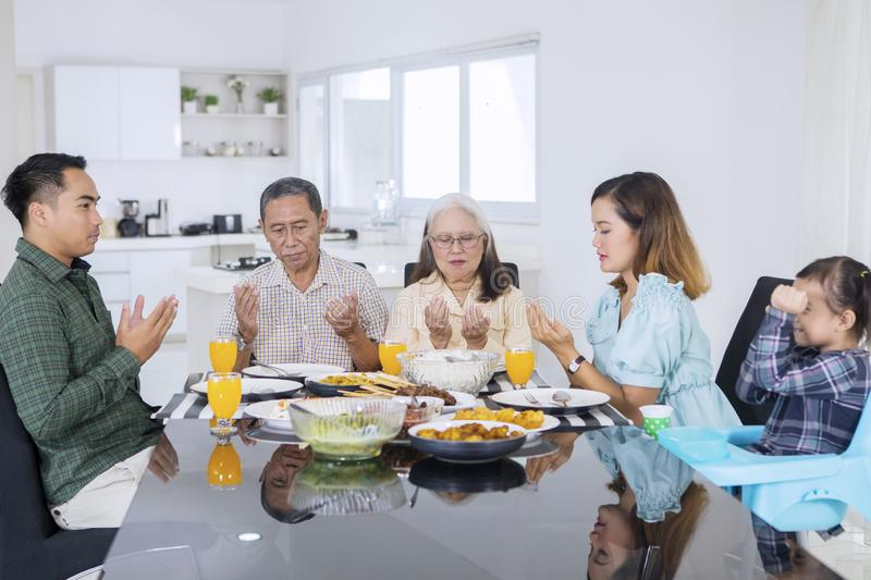 Multi generation family praying before having meals royalty free stock images