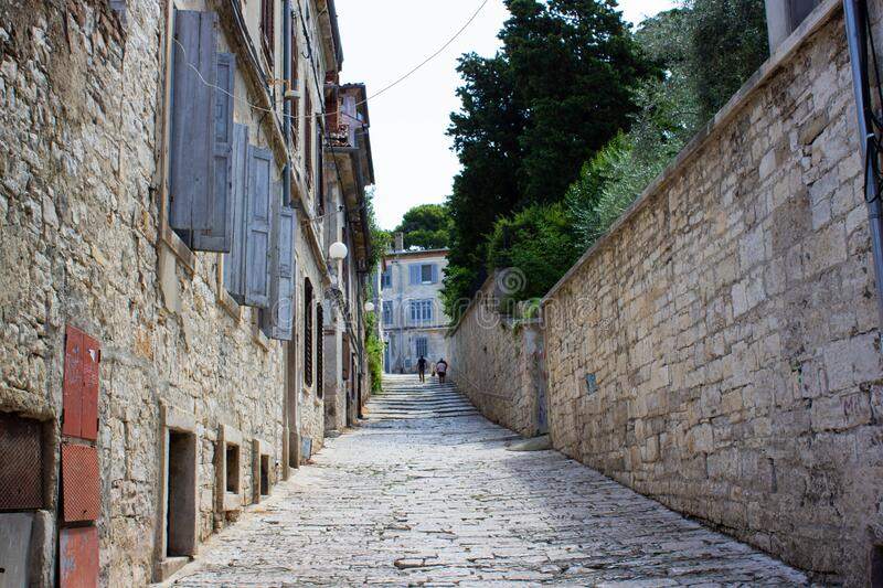 Picture of a narrow colorful stone street in the old town of Pula, Croatia, with steps at the background.  royalty free stock images