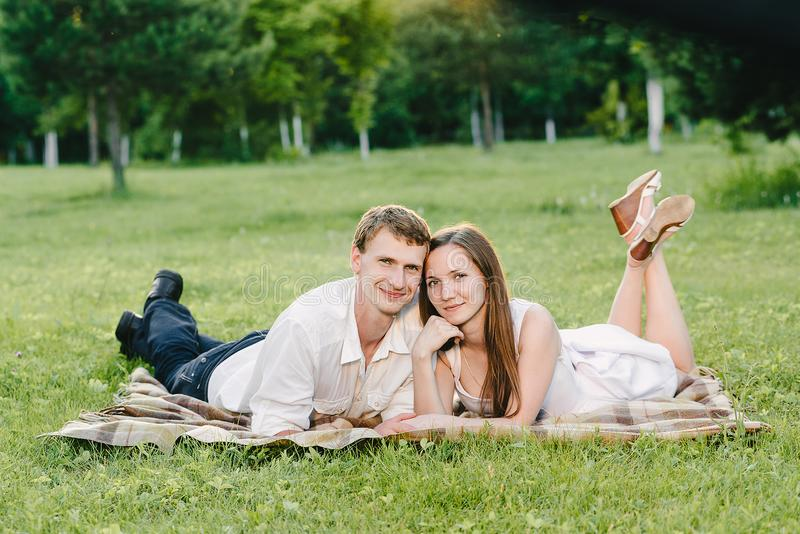 Picture of a nice couple smiling cutely to the camera. Lying on the grass happy together. Love story in the nature royalty free stock photography