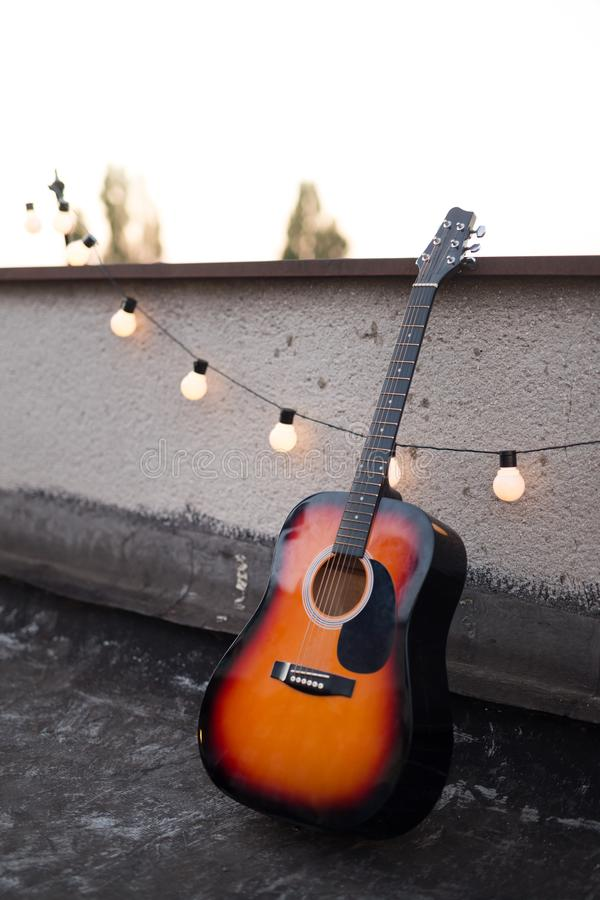 Picture of nice accoustic guitar on rooftop. Picture of nice stringed accoustic guitar on rooftop stock image