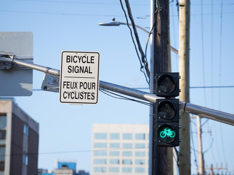 Bicycle Green Traffic Light and North American roadsign in English and French indicating the signal is only for bicycles,. Picture of North American style royalty free stock photos