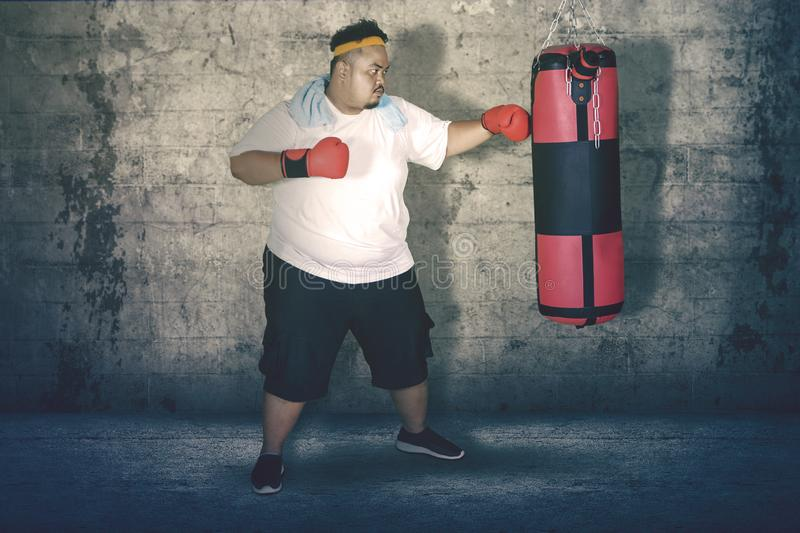Obese man punching a boxing bag. Picture of obese man punching a boxing bag and exercising in the studio stock photo