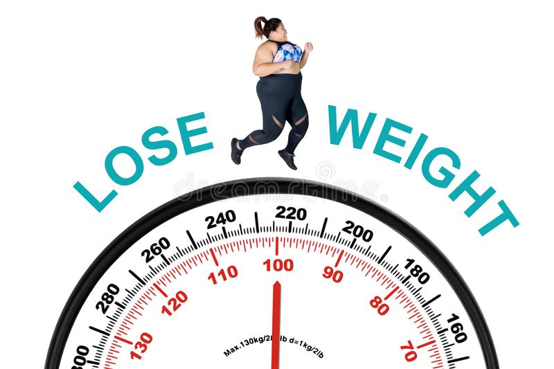 Obese woman running above a weighing scale. Picture of obese woman running above a weighing scale with text of lose weight, isolated on white background stock image