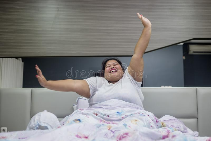 Obese woman stretching hands after wake up royalty free stock photography