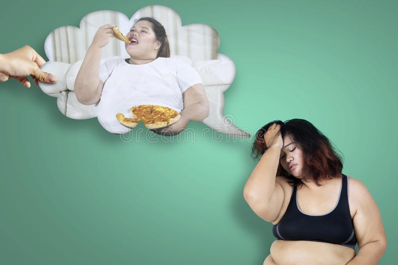 Obese woman thinking her unhealthy habit. Picture of obese women looks depressed while thinking her unhealthy habit royalty free stock photography
