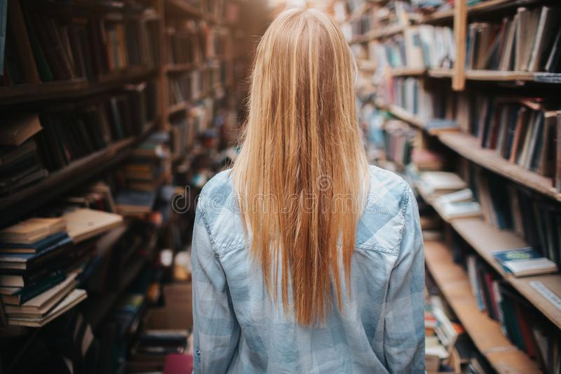 A picture og girl walking among bookshelfs with new and olb books. There is a mess everywhere in the room. She ir making royalty free stock photo