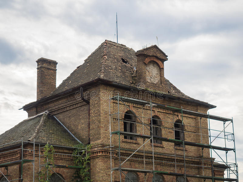 Picture of an old abandoned mansion-house with wooden trestle for alteration work. Background of an old abandoned mansion-house with wooden trestle for stock image