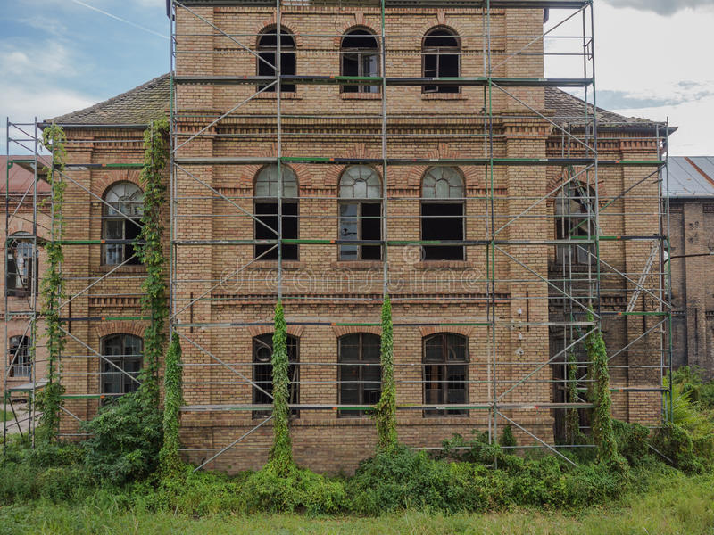 Picture of an old abandoned mansion-house with wooden trestle for alteration work. Verdurous mansion against the background of cloudy sky. Old mansion made of royalty free stock photos