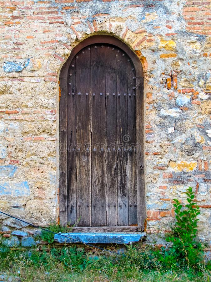 Old rustic wooden door with blue step stock photography