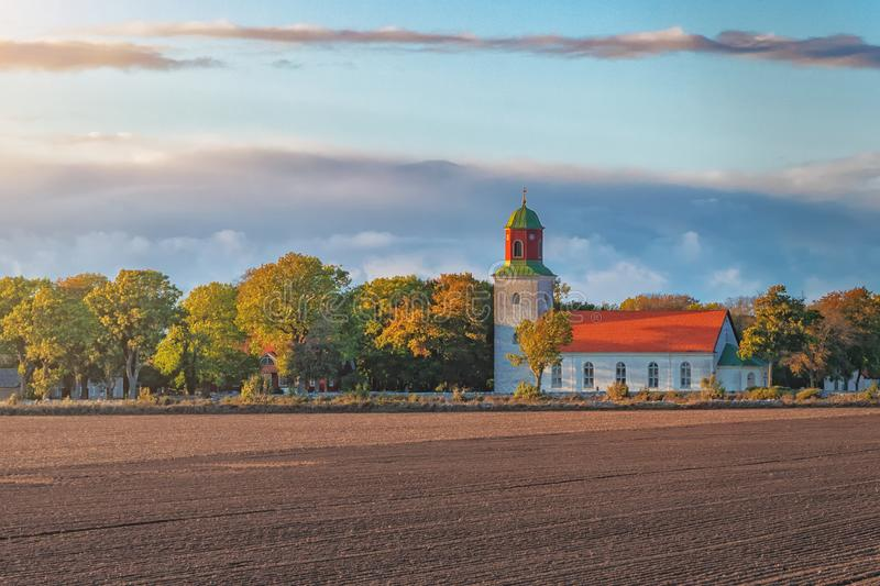 Picture of old scandinavian style church in the field and sunset sun.  stock photography