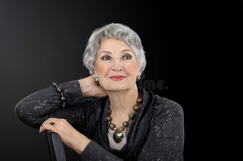Picture of older woman posing with tiger iron eye jewelry set royalty free stock images