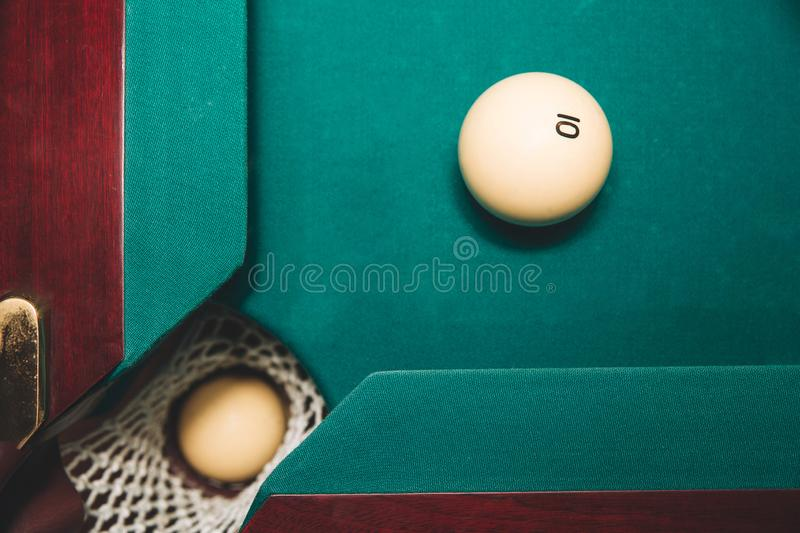 Picture of one billiard ball in billiard hole. Another one is on green bed of table close to hole. Number 10 is on it. royalty free stock photography