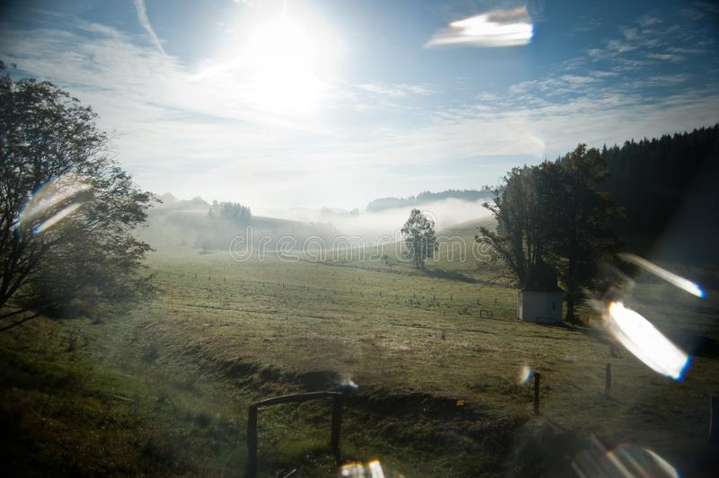 Meadow with a small chapel suffused by sun and haze stock photos