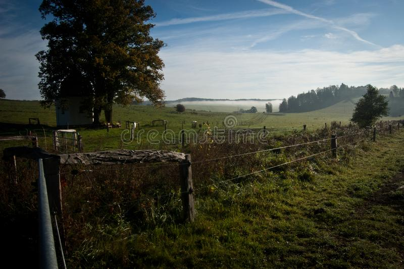 Meadow with a small chapel suffused by sun and haze 3 royalty free stock image