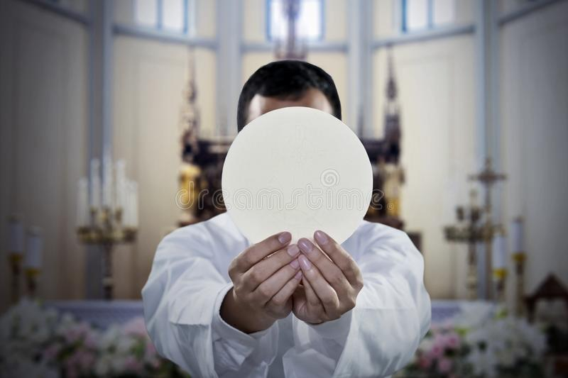 Pastor holding a sacramental bread in church. Picture of pastor celebrating a mass while holding a sacramental bread in the church royalty free stock image