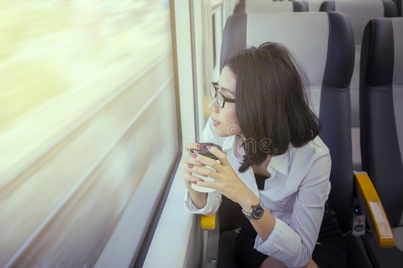Pensive woman holds coffee in airport train stock image