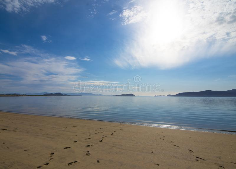 Picture perfect beach with footsteps in the sand.. Perfect sandy beach with footsteps coming from the Sea of Cortez with clear blue water on a sunny day stock photography