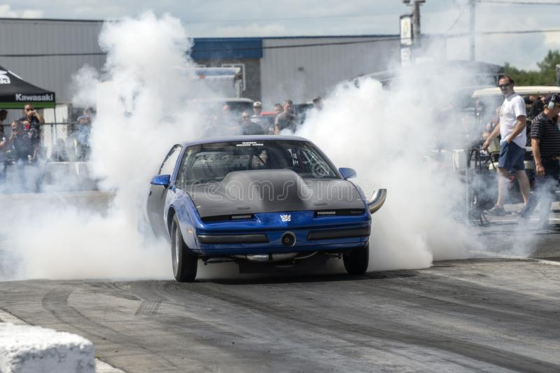 Drag car smoke show. Picture of Pontiac trans am drag car on the track making a smoke show during the john scotti all out august 17, 2017 royalty free stock photo