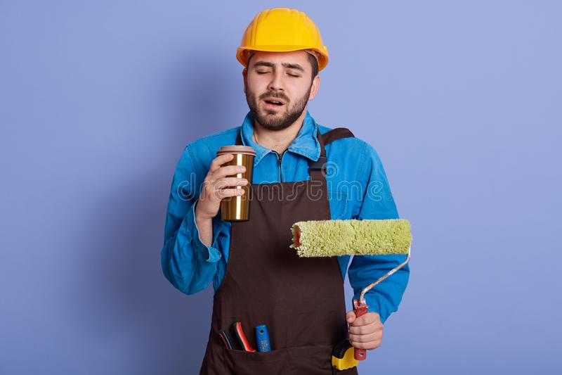 Picture portrait of sleepy tired construction worker closing his eyes, holding thermo mug and roller in both hands, wearing brown stock photography