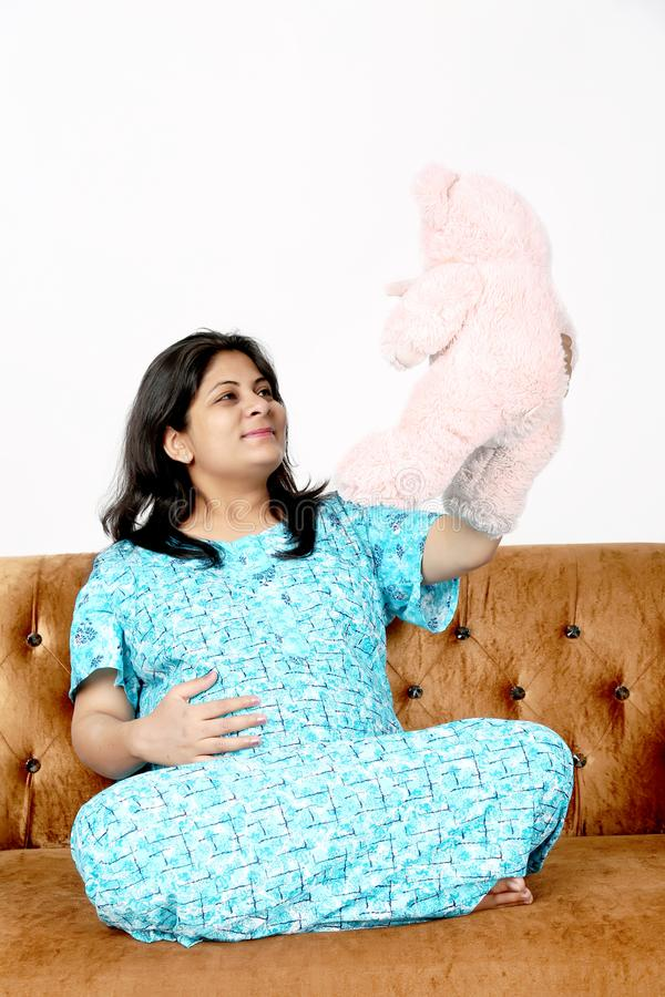Picture of pregnant lady is holding teddy bear in hand with smile face. Isolated on the white background stock photo