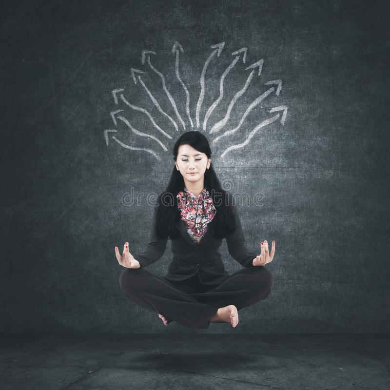 Businesswoman levitating with arrows over her head royalty free stock photos