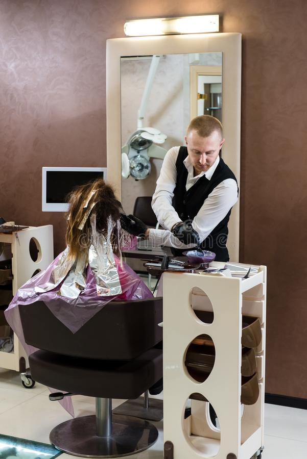 picture of a professional hairstylist working with a girl`s hair in the salon stock image