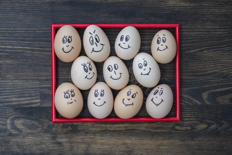 Picture red frame and many funny eggs smiling on wooden wall background, closeup. Eggs family emotion face portrait. Concept funny royalty free stock photography