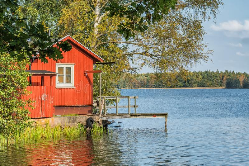 Picture of red wooden scandinavian style house at the lake during autumn stock images