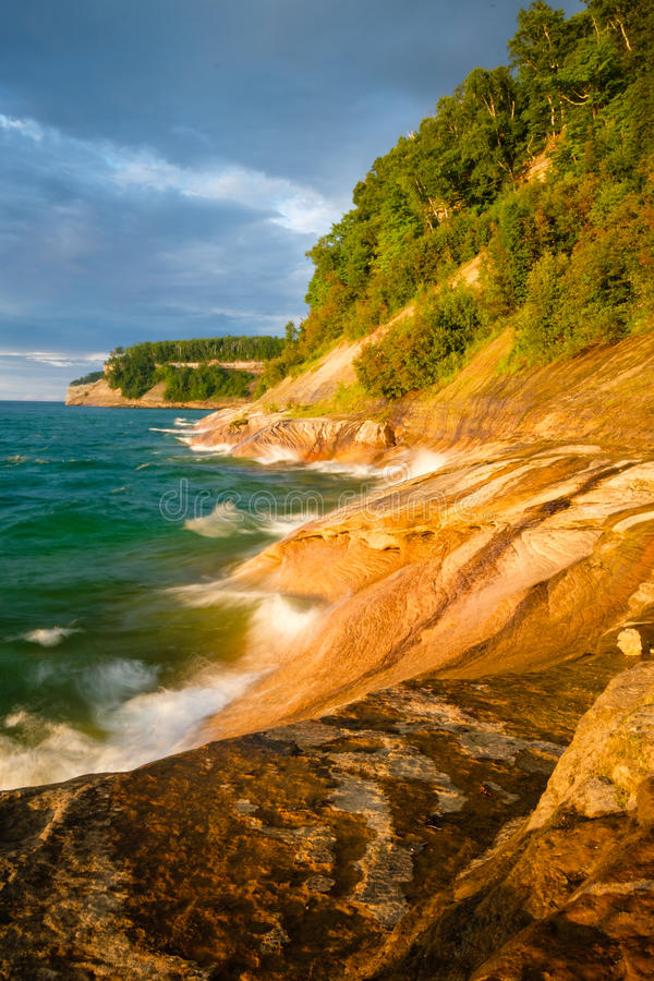 Picture Rocks National Lakeshore at Sunset, Michigan. The colorful sandstone shoreline of Picture Rocks National Lakeshore, near Munising, Michigan, on Lake royalty free stock photo