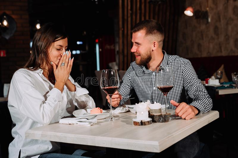 Young happy couple romantic date drink glass of red wine at restaurant, celebrating valentine day. Picture of romantic couple dating in restaurant,Young happy royalty free stock photo