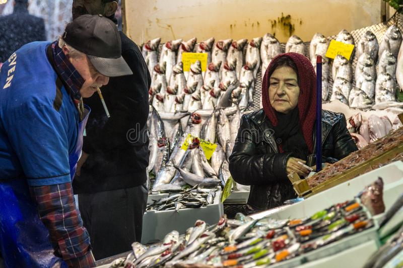 Old woman wearing the islamic scarf buying fish in the fish market of Kadikoy, on the Asian side. royalty free stock photos