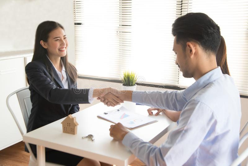 Asian female salesman sit in a modern office room and talk to customers and be satisfied with success. Businesswoman shaking hand with a young couple in office stock image