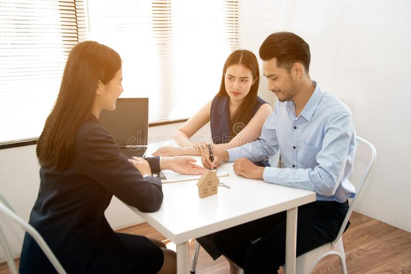 Asian female salesman sit in a modern office room and talk to customers and be satisfied with success. Businesswoman shaking hand with a young couple in office stock photography