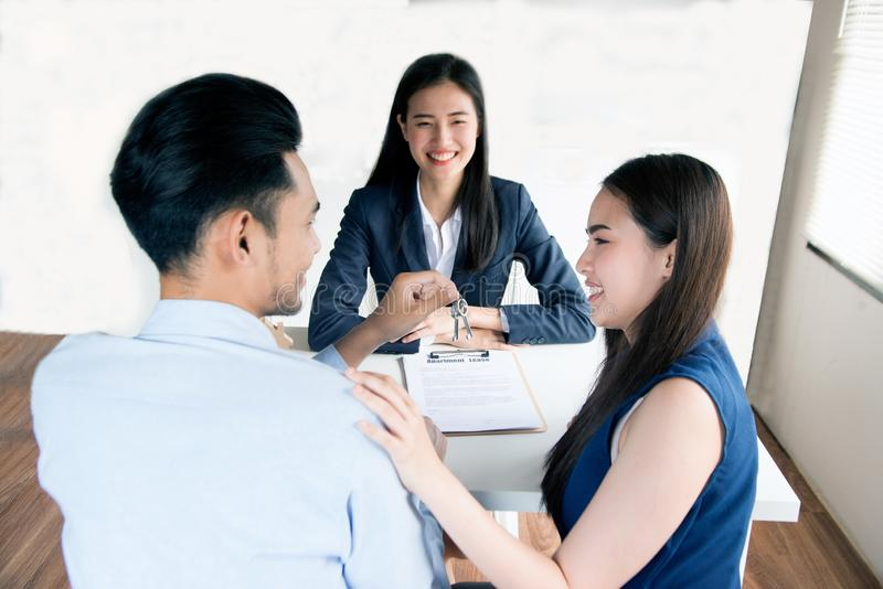 Asian female salesman sit in a modern office room and talk to customers and be satisfied with success. Young Asian business women adviser consulting young royalty free stock images