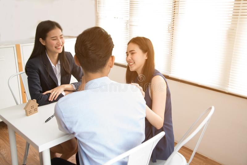 Asian female salesman sit in a modern office room and talk to customers and be satisfied with success. Young Asian business women adviser consulting young royalty free stock photo