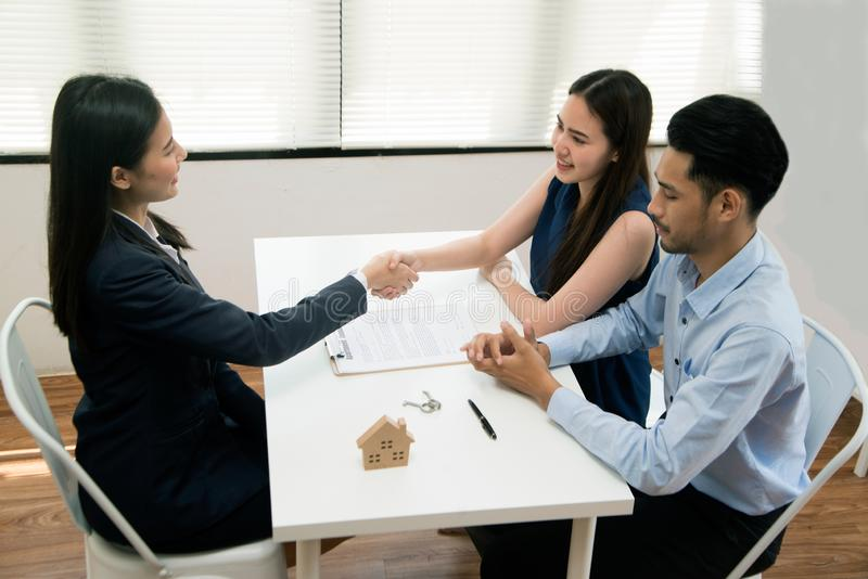 Asian female salesman sit in a modern office room and talk to customers and be satisfied with success. Businesswoman shaking hand with a young couple in office royalty free stock photos