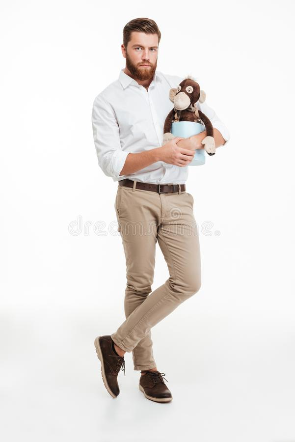 Serious young bearded man holding toy monkey. Picture of serious young bearded man standing over white wall background isolated. Looking camera holding toy stock photography