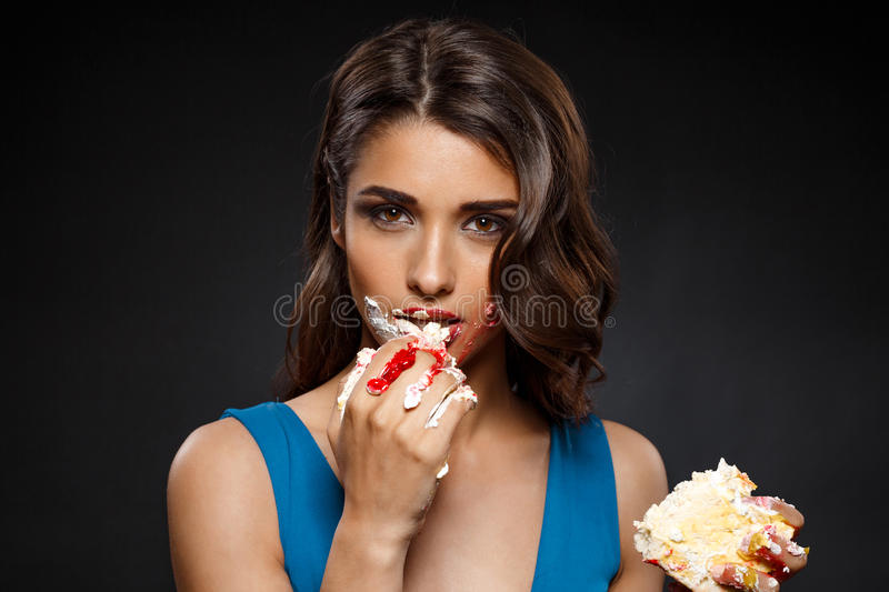 Picture of woman in blue dress eating piece of cake stock photo