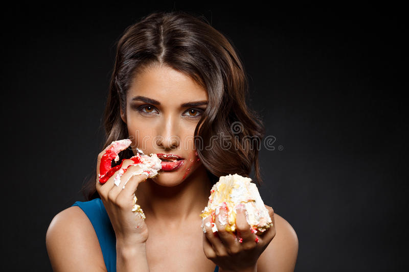 Picture of woman in blue dress eating piece of cake. Over black background royalty free stock photo