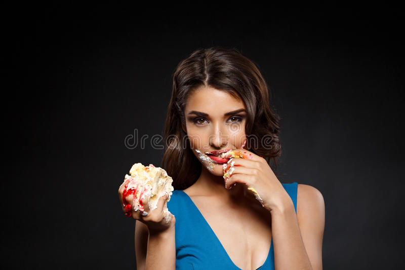 Picture of woman in blue dress eating piece of cake. Over black background stock photos