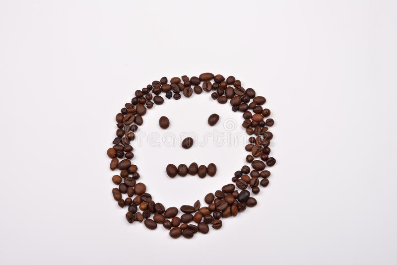 Picture shape face made of coffee beans on white background. Morning pleasure royalty free stock photography