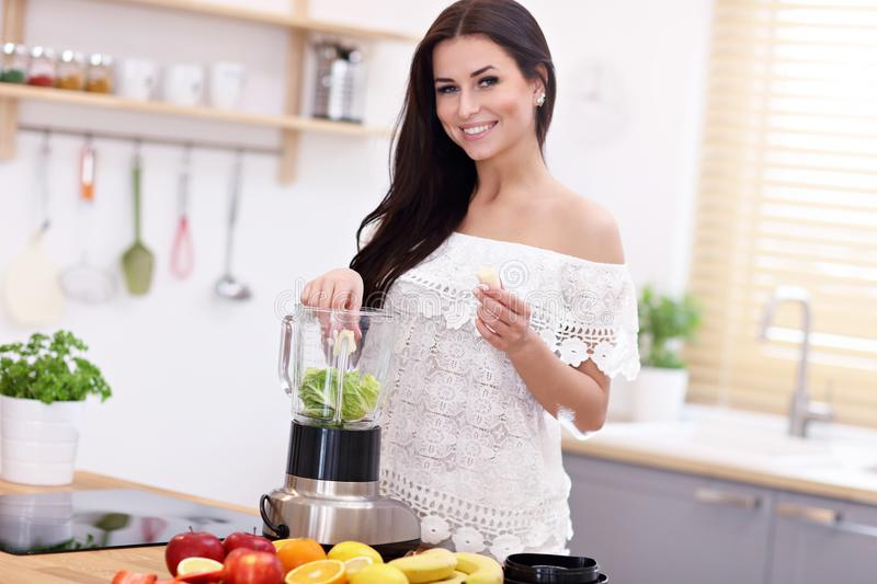 Fit smiling young woman preparing healthy smoothie in modern kitchen royalty free stock photography