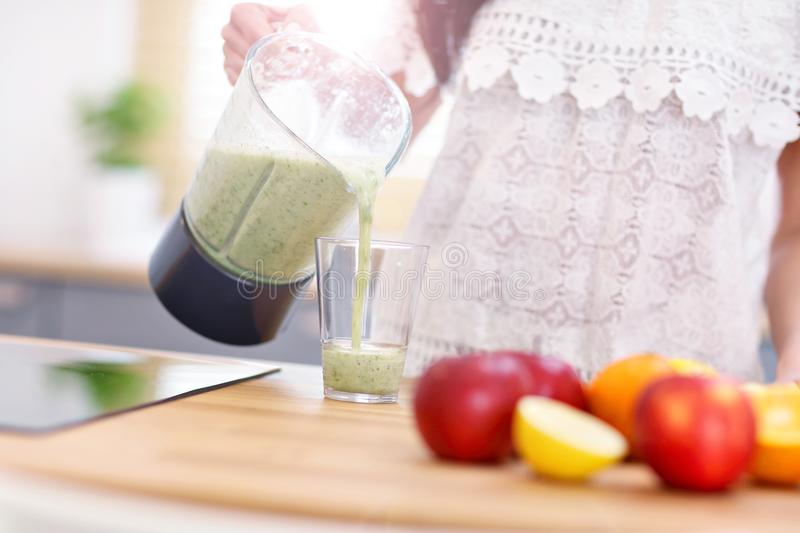 Fit smiling young woman preparing healthy smoothie in modern kitchen royalty free stock image