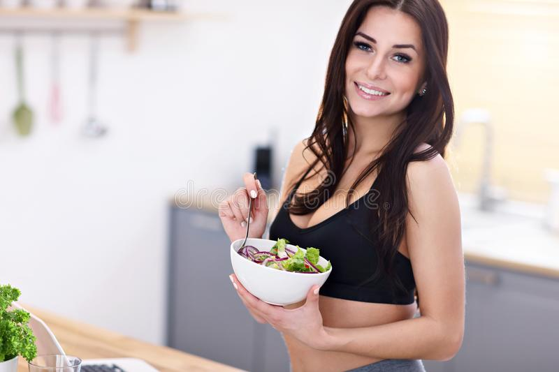 Fit smiling young woman with salad in modern kitchen stock photo